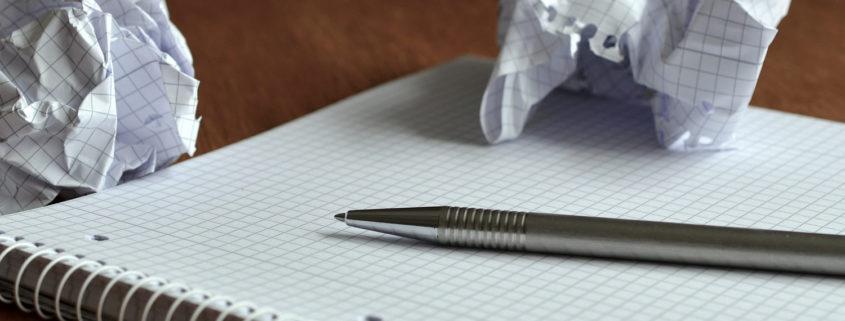 Notizblock mit Stift und zerknüllte Zettel
