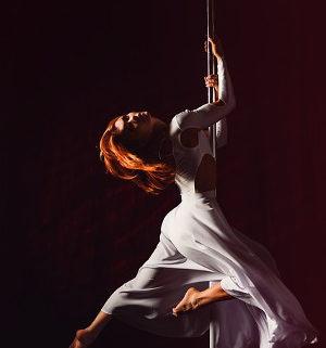 Mädchen schwebt elegant an der Pole Stange