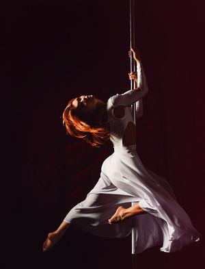 Mädchen schwebt elegant an der Pole Dance Stange