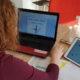 Trainerin beim Vorbereiten der neuen Session mit Laptop und Tablet am Tisch