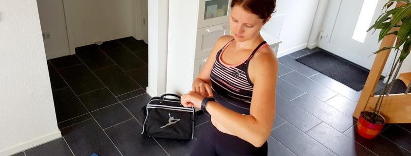 Trainerin Lisa schaut auf die Uhr.